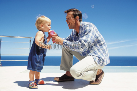 father blowing soap bubbles with toddler