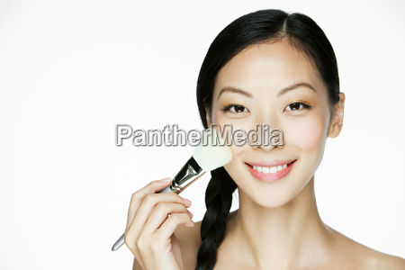 young woman using makeup brush