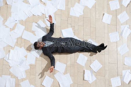 businessman lying on floor with papers
