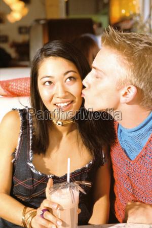 teenage boy kissing girl on cheek