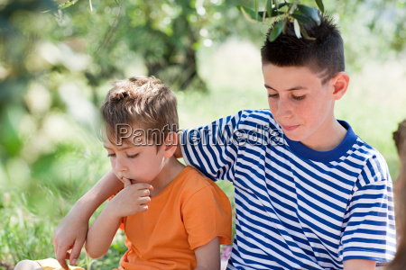 two boys older boy with arm