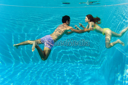 young couple swimming in swimming pool