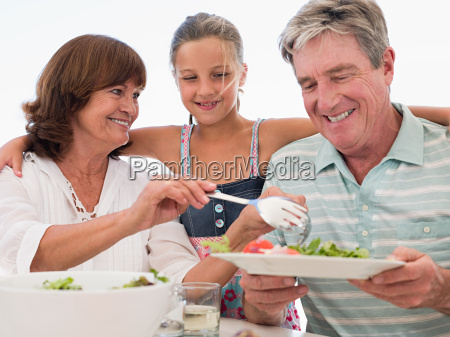 girl and grandparents having meal