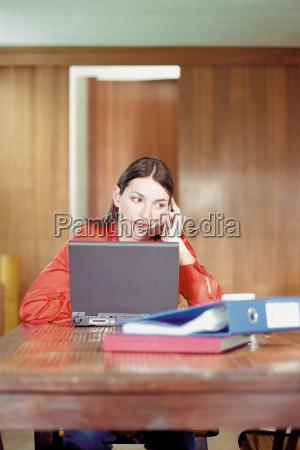 woman using cell phone and laptop