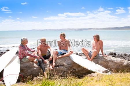 four young male surfer friends chatting