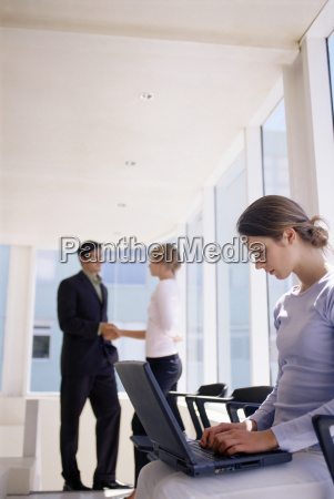 woman using laptop as colleagues shake