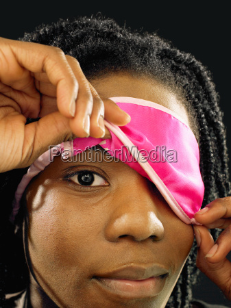 woman lifting eye mask
