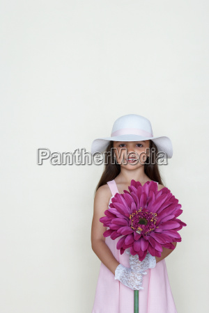 girl holding a large flower