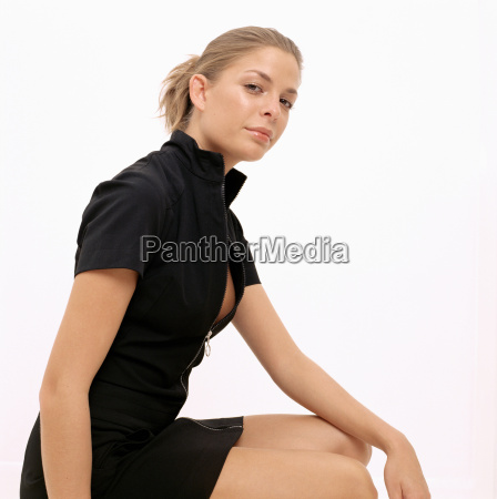 young woman in black dress sitting
