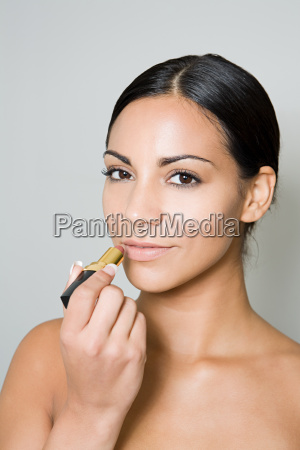 young woman applying lipstick