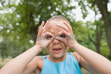 girl looking through her fingers