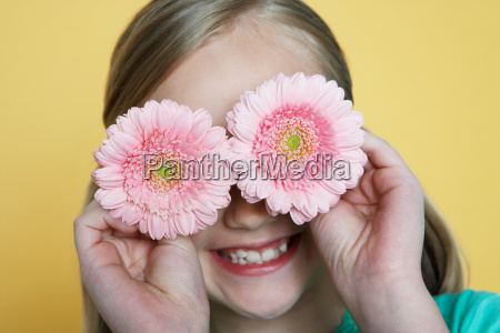 girl holding flowers to eyes