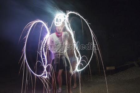 two adult friends making sparkler angel