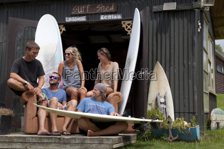 five young adult surfer friends chatting