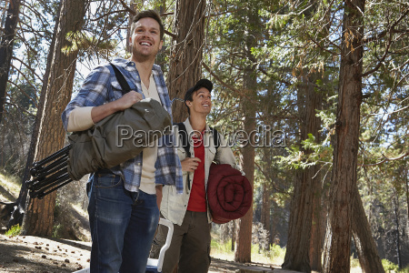 two young men walking in forest