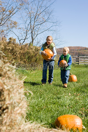 boy and girl carrying pumpkins
