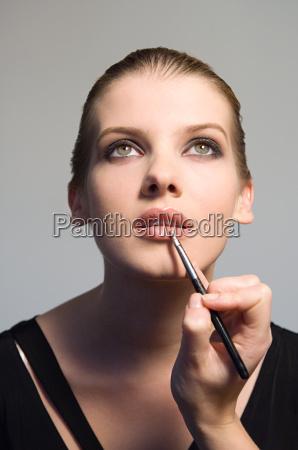 woman having lip gloss applied