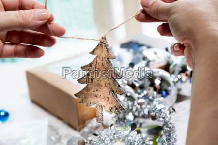 persons hands preparing wooden christmas tree
