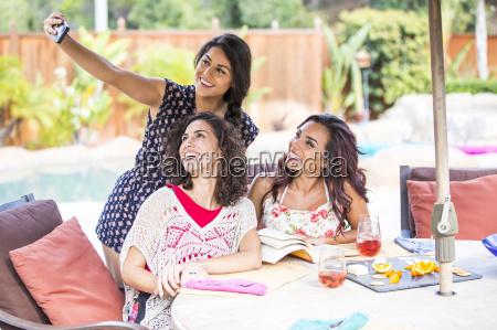 three adult sisters taking self portrait
