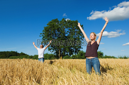 couple in field with arms outstretched