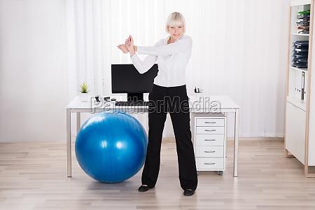 empresaria haciendo ejercicio en la oficina