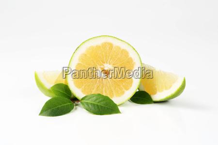 mitad de pomelo verde y rebanadas