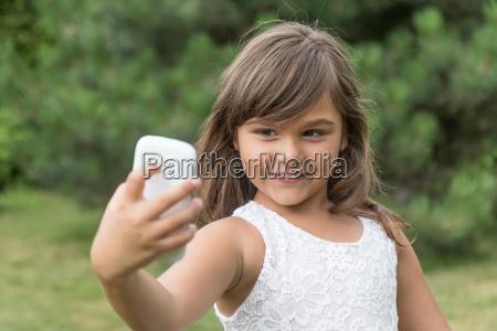 sonriente ninya atractiva esta haciendo selfie