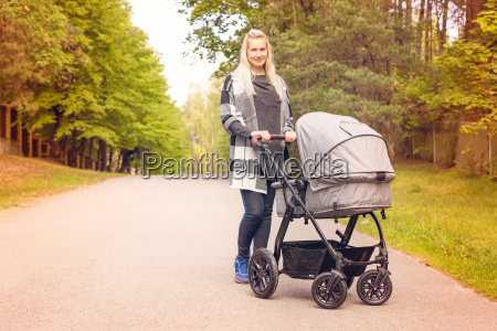 young happy mother with baby carriage