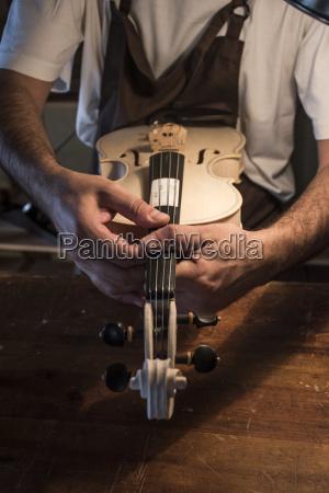 luthier examinando un violin sin matices