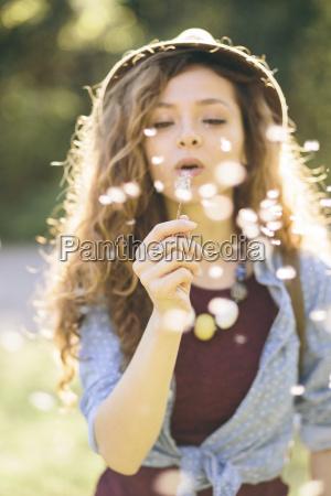 mujer joven soplando diente de leon
