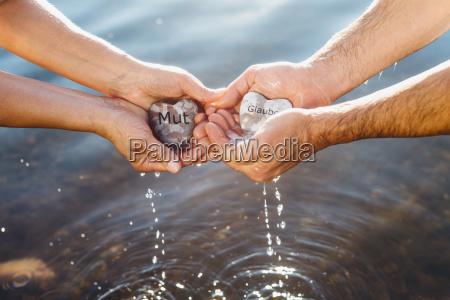 manos sosteniendo piedras coraje y creen
