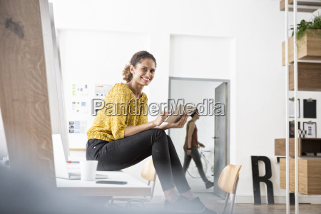 smiling woman sitting on office desk
