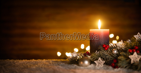 candle with festive decoration and wood