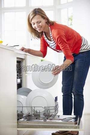 mujer cargando placas en lavavajillas