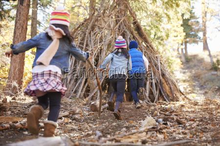 tres ninyos juegan fuera de refugio