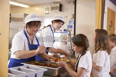 dos mujeres sirviendo comida a una