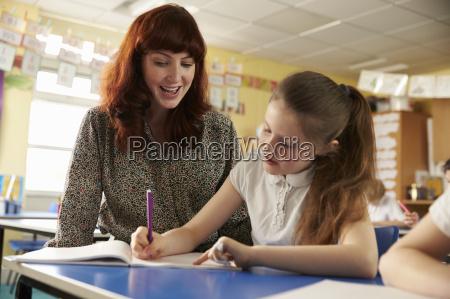 primary school teacher helping with classwork