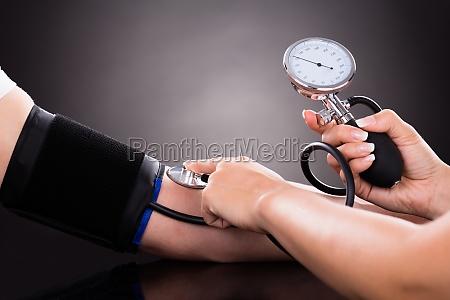 medico comprobando la presion arterial del