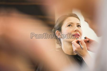 female friend applying lip liner to