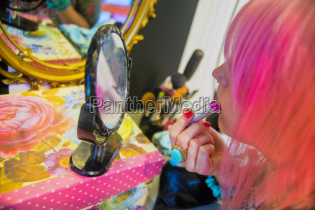 young woman with pink hair putting