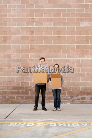 portrait, of, young, couple, holding, cardboard - 19458990