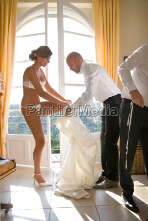 bride getting helped into wedding dress