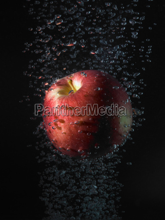 apple in bubbles black background