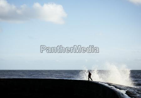person, running, away, from, splashing, wave - 19474820