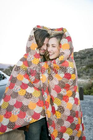 pareja joven envuelta en manta de
