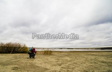 young man hiking crouching taking photograph