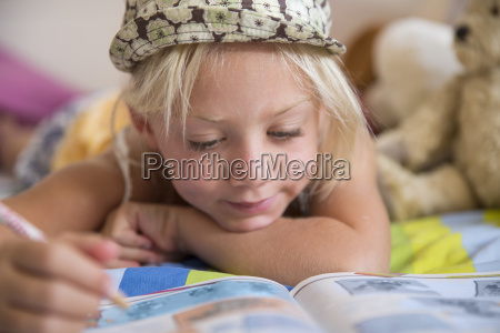 girl lying on bed looking at