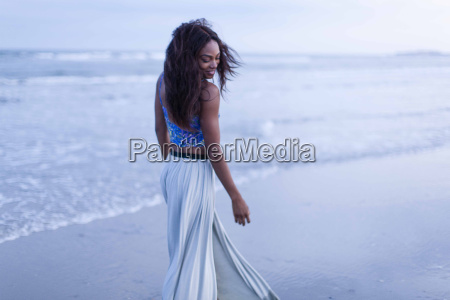 young woman walking on beach looking