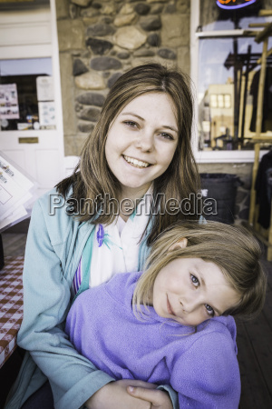 young woman and girl smiling towards