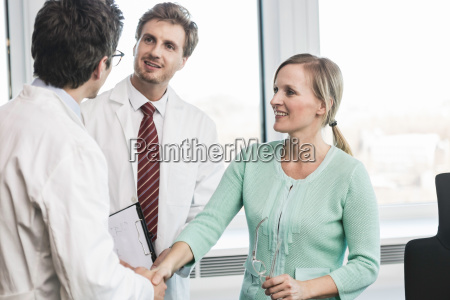 woman shaking hands with man wearing